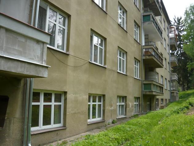 Pohled na fasádu domu z roku 1937, ve kterém je problém se vzlínající vlhkostí